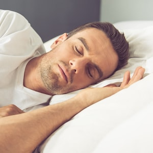 Man asleep as he needs help for sleep apnea and cosmetic dentistry