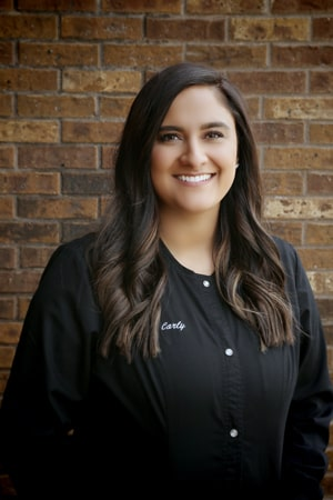 Carly is our clinical coordinator and is smiling in her all black dental uniform at Fox Valley Dental